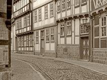 Aleia com as casas suportadas na cidade velha de Quedlinburg no sepia imagens de stock royalty free
