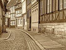 Aleia com as casas suportadas na cidade velha de Quedlinburg no sepia fotografia de stock