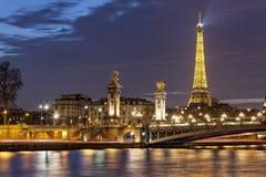 Alejandro III y la torre Eiffel en la noche fotos de archivo