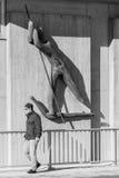 Alemanha, Regensburg, o 5 de fevereiro de 2017, rua photograpy de um caminhante sob uma escultura do ferryman em Regensburg no Pr imagem de stock royalty free
