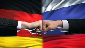 Alemania contra el conflicto de Rusia, relaciones internacionales, puños en fondo de la bandera metrajes