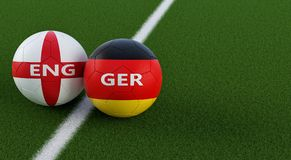 Alemania contra Partido de fútbol de Inglaterra - balones de fútbol en los colores nacionales de Alemania y de Englands en un cam Imagenes de archivo