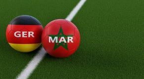 Alemania contra Partido de fútbol de Marruecos - balones de fútbol en alemán colores nacionales y de Marruecos en un campo de fút Imagenes de archivo