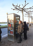 Alemania, sseldorf del ¼ de DÃ: Mujer que toma un libro de una biblioteca de la calle Foto de archivo libre de regalías