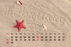 Сalendar with starfish and seashells on sand beach. Februa Stock Photography