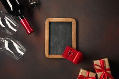 Alentine`s Day with hearts, wine, corkscrew, glasses, gifts, a heart-shaped box and a blackboard. Top view with copy space royalty free stock photo