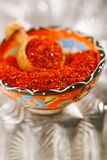 Aleppo Pepper mild chilli flakes. In small bowl on shiny backdrop Royalty Free Stock Photography