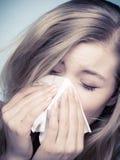 Alergia da gripe. Menina doente que espirra no tecido. Saúde imagens de stock