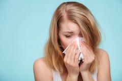 Alergia de la gripe Muchacha enferma que estornuda en tejido salud