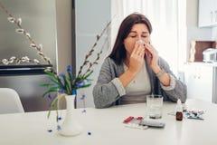 Alergia de la primavera Mujer joven que estornuda debido a las flores rodeadas con las píldoras en cocina Concepto estacional de  foto de archivo