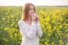 Alergia del polen, muchacha que estornuda en un campo de la rabina de flores Fotos de archivo