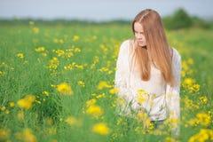 Alergia do pólen, menina que espirra em um campo das flores Foto de Stock Royalty Free