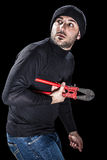 Alert Burglar. A burglar wearing black clothes holding huge wire cutters over black background stock photography
