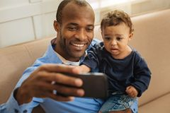 Alert daddy amusing his kid. Amusing his kid. Handsome alert young afro-american daddy smiling and holding his cute little curly-haired son while taking selfies Royalty Free Stock Photos
