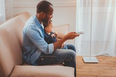 Alert father babysitting his child. Caring dad. Glad loving daddy holding a remote control and babysitting his son stock images