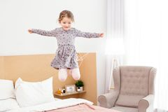 Alert girl jumping on bed. I feel happy. Inspired little girl smiling and having fun at home Royalty Free Stock Photography