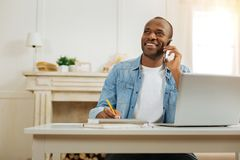 Alert man talking on the phone and working. Hey boss. Attractive exuberant young afro-american businessman smiling and talking over the phone and holding a Royalty Free Stock Photo