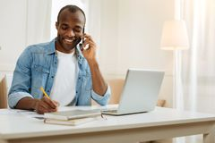 Alert man talking on the phone and writing. Listening. Attractive inspired young afro-american businessman smiling and talking over the phone and writing while Stock Photography