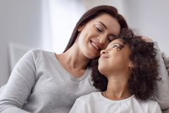 Alert mother embracing her daughter. My dear. Pretty content dark-haired women smiling and hugging her little daughter while looking at each other Stock Image