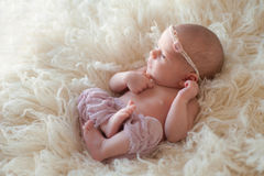 Alert Newborn Baby Girl. Beautiful portrait of an alert 10 day old newborn baby girl. She is awake and curled up oon her back on a cream colored flokati rug royalty free stock image
