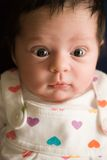 Alert Newborn Baby Infant. Three week old bright-eyed alert newborn baby infant girl wearing heart print dress Stock Photography