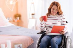 Alert smiling disabled woman holding a cup and a notebook Stock Photos