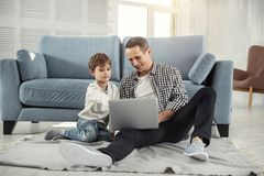Alert son and daddy using the laptop. Watching a film. Nice joyful fair-haired boy smiling and sitting on the floor with his father and they using their laptop stock photography