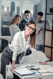 Alert woman standing at her table stock images