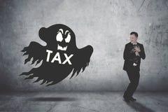 Alerte de fonctionnement d'homme d'affaires chassé par un fantôme d'impôts Photographie stock libre de droits