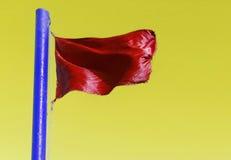Alerte sur le bleu de mât de drapeau sur un fond jaune Photos stock