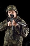 Alerted soldier keeping a gun. In studio Stock Photography