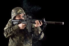 Alerted soldier keeping a smoking gun. Isolated Royalty Free Stock Photo