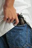 Alertness. Close up of a revolver holded in jeans back pocket stock photo