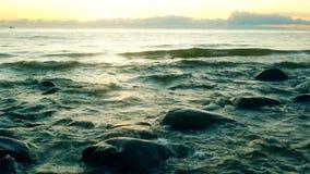 Alesaje de marea El barco flota en el fondo del sol naciente y de las nubes almacen de metraje de vídeo