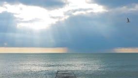 Alesaje de marea La puesta del sol en el mar, los rayos del sol hace su manera a través de las nubes almacen de video
