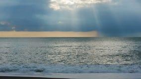 Alesaje de marea La puesta del sol en el mar, los rayos del sol hace su manera a través de las nubes almacen de metraje de vídeo