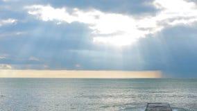 Alesaje de marea La puesta del sol en el mar, los rayos del sol hace su manera a través de las nubes metrajes