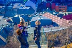 ALESUND NORGE - APRIL 04, 2018: Kvinna som poserar för bild från sikten för öga för fågel` s av den Alesund portstaden på det väs Royaltyfria Foton