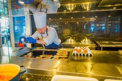 ALESUND, NORWAY - APRIL 04, 2018: Indoor view of cheff man cooking in a luxury kitchen inside of Hurtigruten voyage in Royalty Free Stock Photography