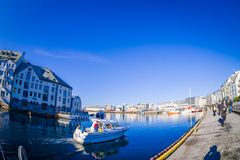 ALESUND, NORWAY - APRIL 04, 2018: Outdoor view of Alesund port town on the west coast of Norway, with some boats sailing. At the entrance to the Geirangerfjord Royalty Free Stock Image