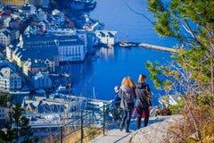 ALESUND NORWEGIA, KWIECIEŃ, - 04, 2018: Niezidentyfikowani ludzie chodzi ptasi ` s przyglądają się widok Alesund portu miasteczko Obrazy Royalty Free