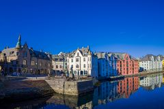 Alesund Norwegia, Kwiecień, - 04, 2018: Plenerowy widok wodny kanał z domami i portem w miasteczku na pięknym słonecznym dniu wew Fotografia Royalty Free