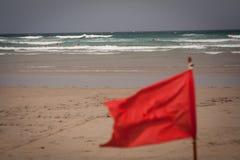 Aleta de bandera roja en la playa fotos de archivo
