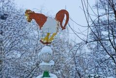Aleta de tempo sob a forma de um galo colorido do ferro na parte superior do telhado Fotos de Stock Royalty Free