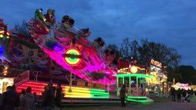 Aleta del paseo del Funfair (Fahrgeschäft) en la feria de diversión alemana (Kirmes) en la noche 4K almacen de metraje de vídeo