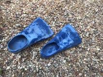 Aletas de natación azules en arena de la roca Foto de archivo libre de regalías