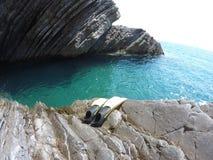 Aletas para zambullirse, y el agua azul del mar, costa rocosa, Imagenes de archivo