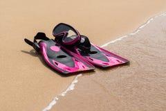 Aletas rosadas en la arena de la playa con la onda en fondo Foto de archivo libre de regalías