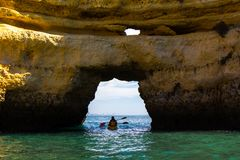 Aleutian kayak moving trough grotto towards sea Stock Image