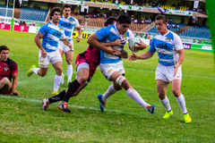 Alex Muller of Argentina at Safaricom Sevens 2014. Argentinian rugby star Alex Muller runs through a tackle during the Safaricom Sevens Finals match against The royalty free stock photos